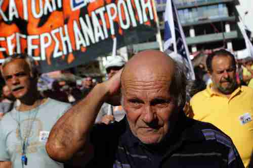 An elderly man marches with protesters in front of the Greek parliament on Tuesday (AFP)