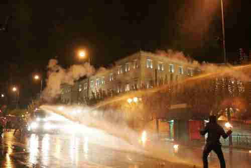 A protester on Wednesday about to throw a petrol bomb is struck by water cannon (Guardian)