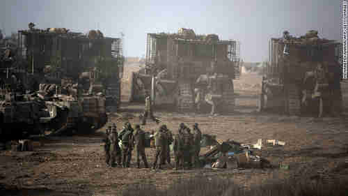 Israeli soldiers gather next to their armored bulldozers stationed on Israel's border with Gaza on Saturday, awaiting orders for the ground invasion (CNN)