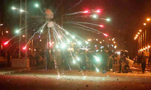 Protesters throw fireworks at police in Cairo on Friday (Reuters)