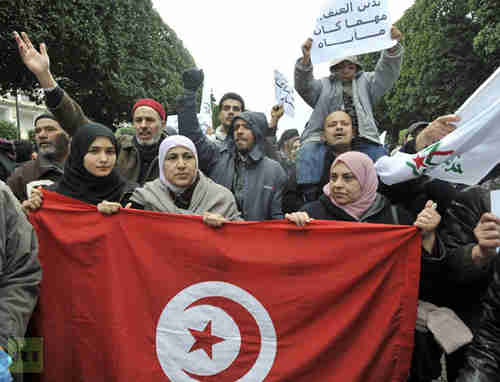 Ennahda supporters hold up Tunisian flag on Saturday (AFP)