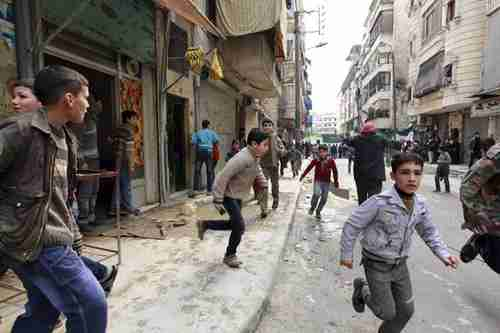 People run after hearing a missile strike in Aleppo on Friday (Reuters)