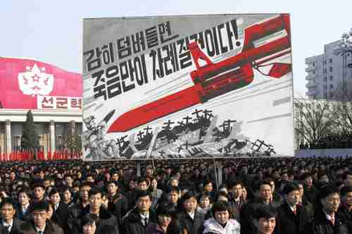 N. Korean rally in Pyongyang in front of billboard that depicts a large bayonet pointing at U.S. soldiers and reads, 'If you dare invade, only death will be waiting for you!' (AP)