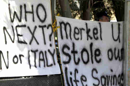 Protesters holds up protest signs in Nicosia, Cyprus (AP)