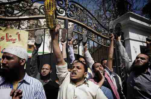 Egyptian protesters raise their shoes outside the Iranian ambassador's residence in Cairo (AFP)