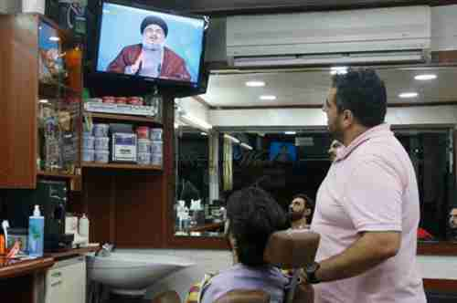 People watch Nasrallah on television on Tuesday (Daily Star)