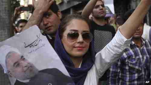 Female supporter holding up picture of Rouhani at a June campaign event.  Her loose hairscarf is an act of rebellion against the hardliners.  (BBC)