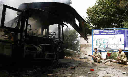 Bombed out bus next to women's university campus sign on Saturday (Dawn)