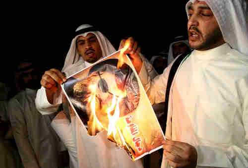 Kuwaiti protesters burn a picture of Hezbollah leader Hassan Nasrallah (AFP)