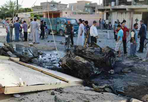 Scene of two parked car bombs north of Baghdad on Sunday (AP)
