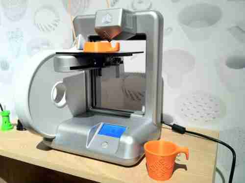3D printer printing a cup -- it could just as easily have been a gun