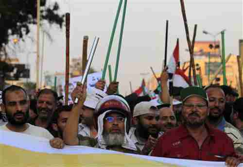 Muslim Brotherhood members wave sticks and shout slogans in support of president Mohamed Morsi (Reuters)