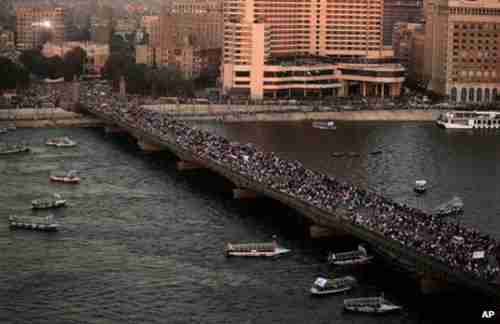 Anti-Morsi demonstrators cross a bridge in Cairo on Friday (BBC)