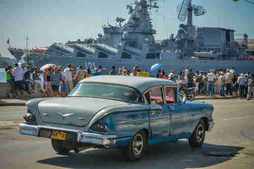 A 1950s U.S. car passes Cubans waving at the Russian 'Moskva' missile cruiser in Havana on Saturday (AFP)
