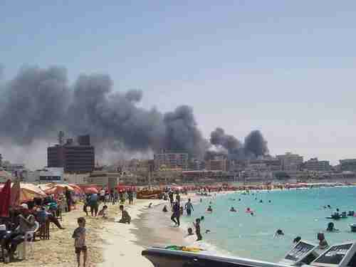 Egyptians enjoy the beach while fires and riots burn in the background
