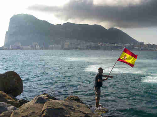 A fisherman holds a Spanish flag during a protest in the bay of Algeciras, near the Rock of Gibraltar, on Sunday (AP)
