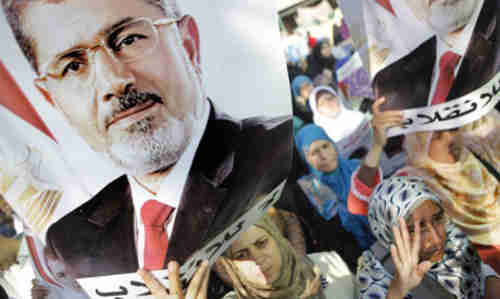 Morsi supporters hold posters with Morsi's face and words in Arabic that read 'No to the coup' on Monday (AP)
