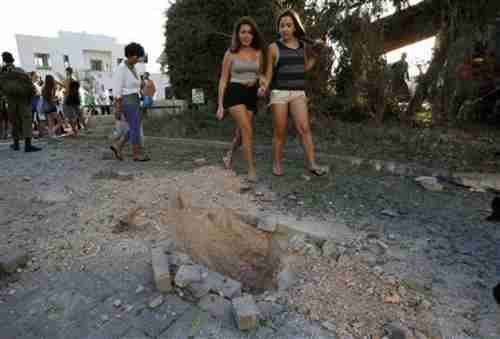 Two hot chicks walk past damage caused by a rocket fired from Lebanon into Israel (Reuters)