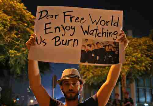 Syrian man in front of United Nations building in Beirut holds up placard saying, 'Dear Free World, Enjoy watching us burn.' (AP)