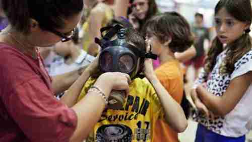 Israeli child being fitted with a gas mask