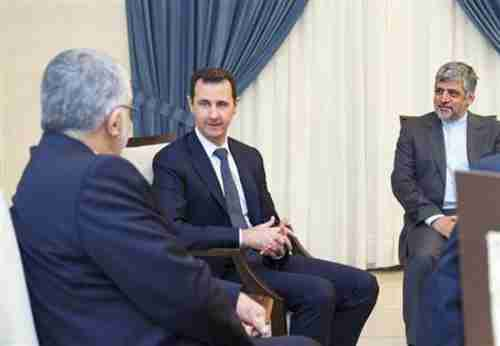 Bashar al-Assad smiles on Monday at a meeting where he's presumably celebrating the number of Sunni women and children civilians he's torturing and killing (Reuters)