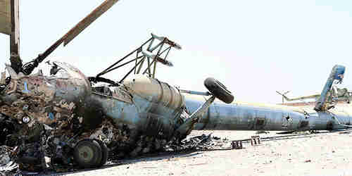 A destroyed Russian-made helicopter that belonged to the Syrian army is seen at the Minnigh military airport (Reuters)