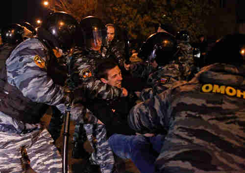 Moscow police detain a man on Sunday (Reuters)