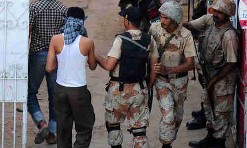 Paramilitary soldiers arrest suspects in a residential area in Karachi (AFP)