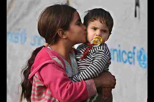 A Syrian girl in a Lebanon refugee camp kisses her younger brother.  (AP)