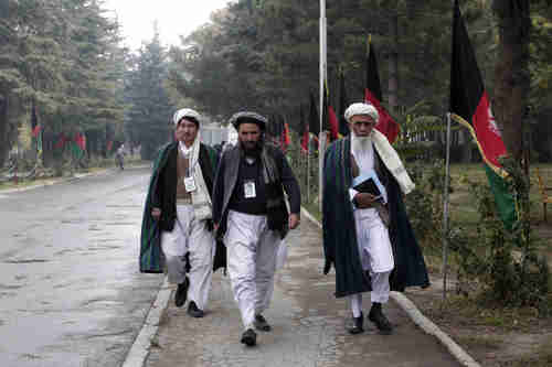 Loya Jirga delegates walk on the streets of Kabul, Afghanistan, on Friday (AP)