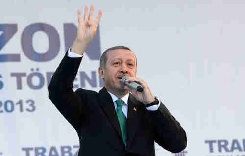 Erdogan on Saturday gives the four-finger salute used by Muslim Brotherhood supporters (AFP)