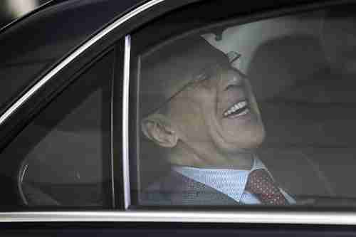 Russia's foreign minister Sergei Lavrov laughs hysterically as his car pulls away from the conference venue (AFP)