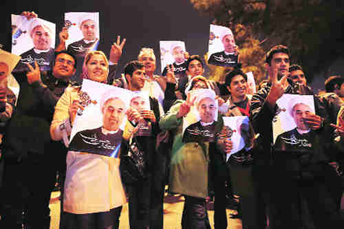 Jubilant Iranians holding posters of president Hassan Rouhani welcome the return of victorious negotiator Javad Zarif in Tehran on Sunday (AP)