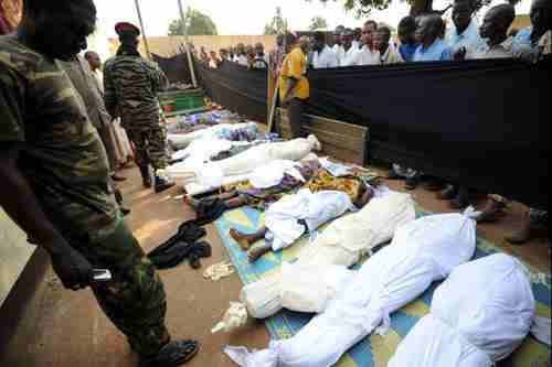 People stand near bodies found lying in a mosque and in its surrounding streets in the Central African capital Bangui on Thursday, after overnight violence (AFP)