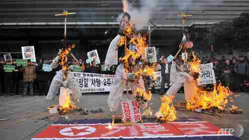 South Koreans burn effigies of North Korean child dictator Kim Jong-un and his late father (AFP)
