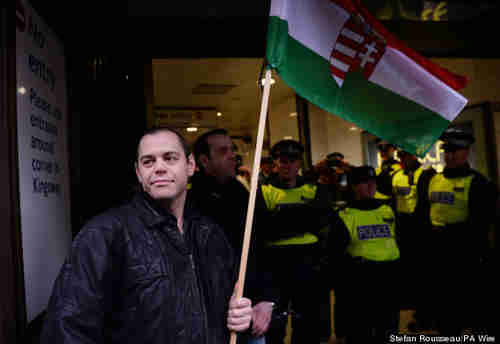Gabor Vona in London on Sunday, carrying a Hungarian flag, protected from anti-fascist activists by police