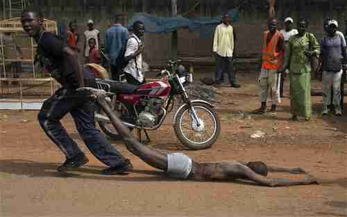 A man drags the corpse of the man who was lynched by CAR soldiers on Wednesday (AFP)