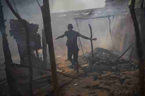 A Christian man runs through looted and burning homes of Muslims who have fled for their lives (Nat. Geographic)