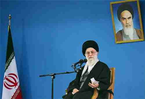 Ayatollah Khamenei, sitting underneath a picture of his predecessor, Ayatollah Khomeini (Fars)