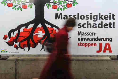 The caption says: 'The excess is harmful! Stop mass immigration - YES.'  I'm not sure what the tree symbolizes, but in the picture its roots are strangling Switzerland.