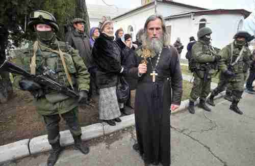 An Orthodox priest holds a crucifix next to armed men in military fatigues blocking access to a Ukrainian border guards base in Crimea on Sunday (AFP)