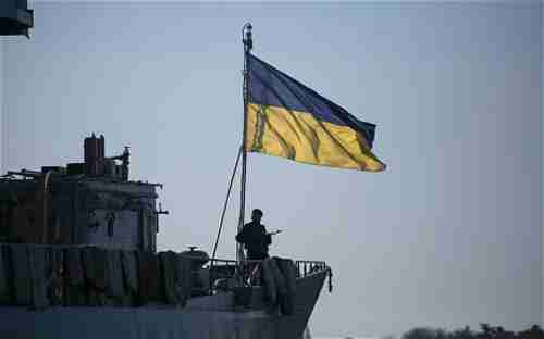 A member of the Ukrainian Navy stands guard on top of the Ukrainian navy command ship Slavutych in Sevastopol.  Russian ships are blockading the Ukrainian ships.