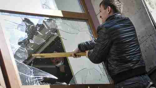 Pro-Russian protester breaks a window of a government building in Donetsk on Sunday (BBC)