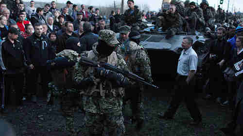 Pro-Russian activists block Ukrainian soldiers in armored personnel carriers in east Ukraine on Wednesday (AFP)