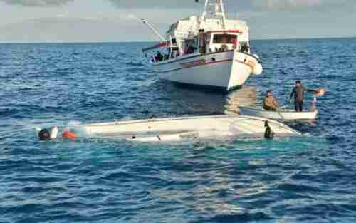 A fishing boat approaches the capsized vessel that had had 65 passengers on Monday (Kathimerini)