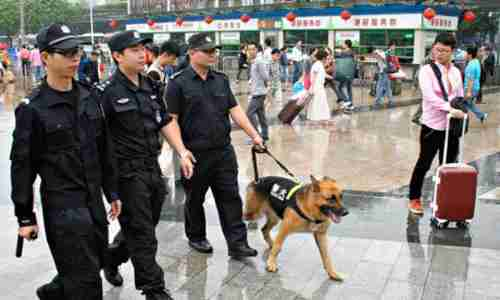 Police officers patrol at Guangzhou railway station after Tuesday's knife attack (Getty)