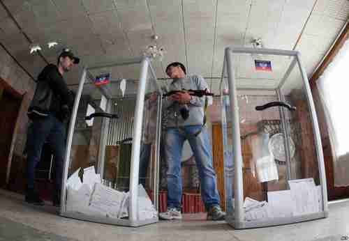 Armed Pro-Russian activists stand guard near clear plastic ballot boxes (AFP)