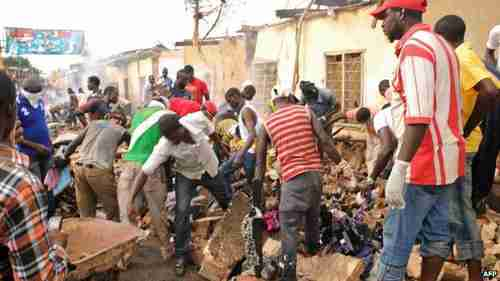 Shopkeepers in Jos salvage belongings after the attack (AFP)