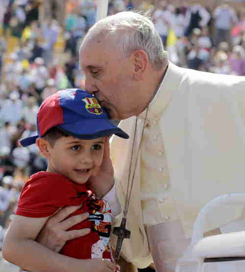 Pope Francis kisses a boy before celebrating a mass in Amman on Saturday (Getty)