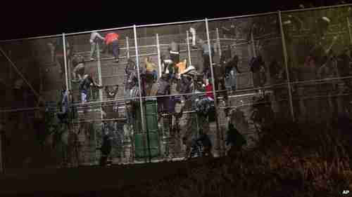 A flood of migrants scaled the metallic fence dividing Morocco from Metilla (AP)